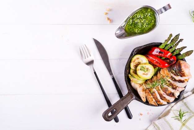 Chicken breast grill with bbq vegetables and pesto sauce in a cast iron pan on white Premium Photo