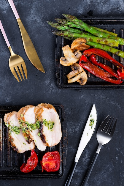 Chicken breast grill with bbq vegetables and pesto sauce in a cast iron pan Premium Photo