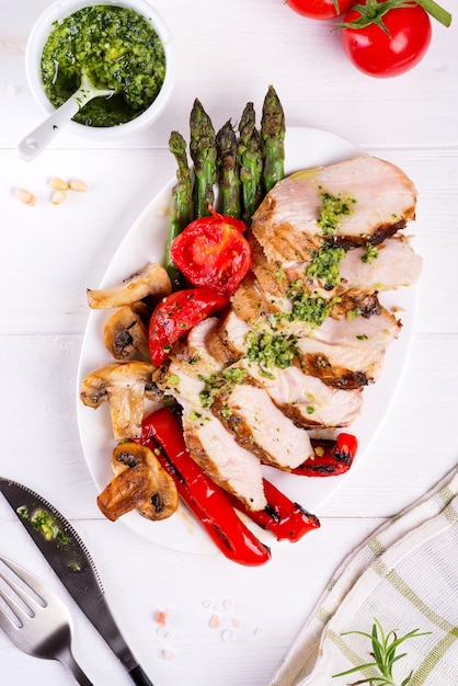 Chicken breast grill with bbq vegetables and pesto sauce in a plate on wood Premium Photo