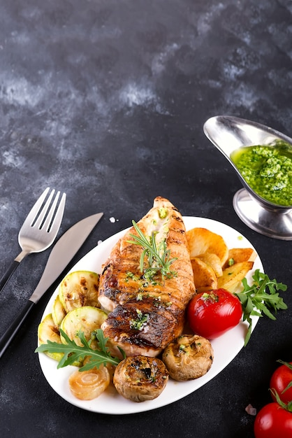 Chicken breast grill with bbq vegetables and pesto sauce in a plate Premium Photo