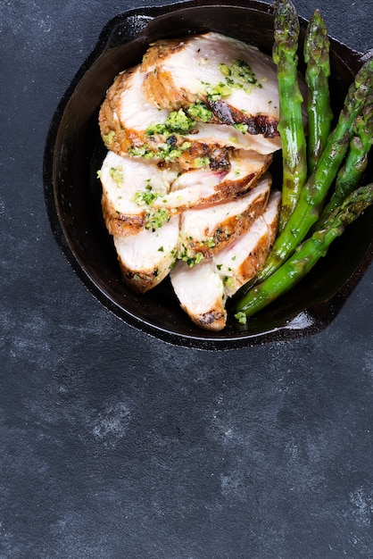 Chicken breast grill with green asparagus and pesto sauce in a cast iron pan Premium Photo
