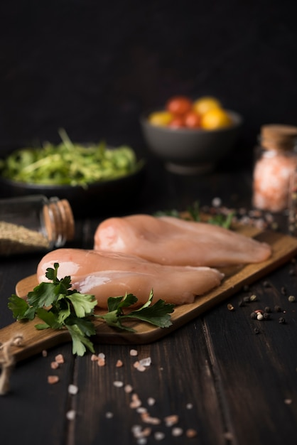 Куриная грудка на деревянной доске с ингредиентами Бесплатные Фотографии