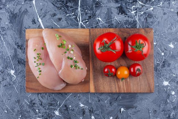 Petto di pollo e pomodori su una tavola sulla superficie blu Foto Gratuite