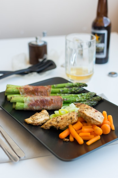 Chicken breasts steak with asparagus wrapped in bacon Free Photo