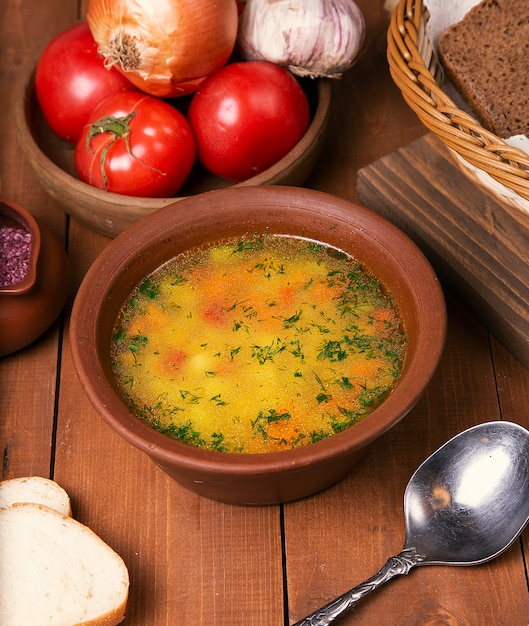 Chicken broth vegetable soup with chopped parsley in pottery bowl. Free Photo