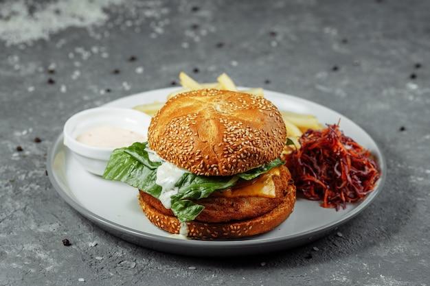 Куриный бургер с картофелем и салатом на старом бетоне. Premium Фотографии
