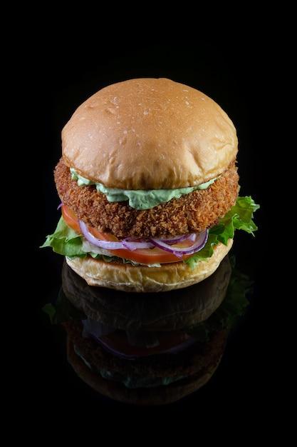 レタス、トマト、紫の玉ねぎ、手作りのマヨネーズを黒のバックゴーランドに添えたチキンバーガー。おいしい。 Premium写真