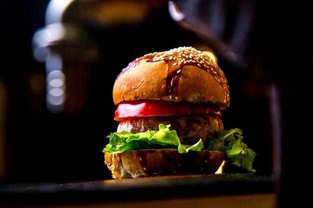 Hamburger del pollo sulla vista laterale della lattuga al pomodoro del bordo di legno Foto Gratuite