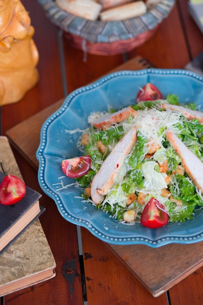 Chicken caesar salad with chopped parmesan cheese fresh lettuce and tomatoes, crackers in blue plate. Free Photo