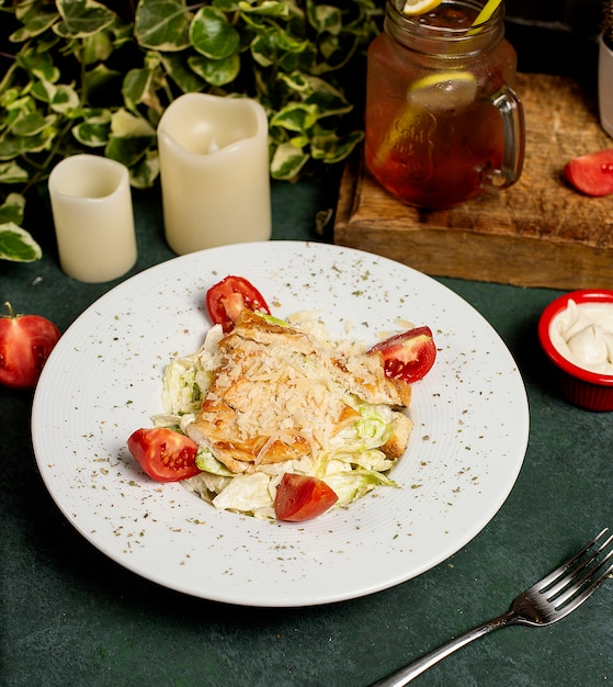 Chicken caesar salad with chopped parmesan, lettuce and tomatoes Free Photo