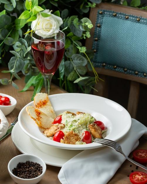 Chicken caesar salad with glass of wine Free Photo