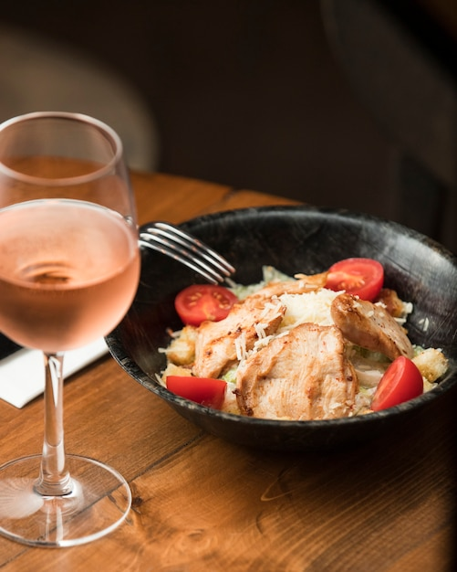 Chicken caesar salad with rose wine Free Photo