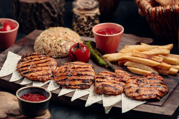Chicken cotlets with fries, grilled vegetables and rice garnish. Free Photo
