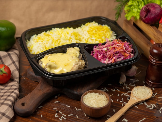 Chicken in cream melted cheese sauce with rice garnish and cabbage carrot salad takeaway Free Photo
