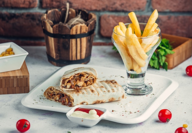 Chicken doner in lavash with french fries in the plate Free Photo