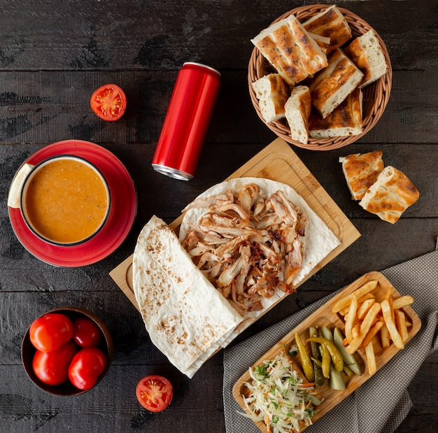 Chicken doner slices on flatbread, served with lentil soup and side dishes Free Photo