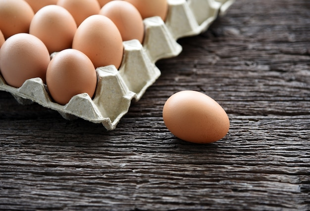 Chicken egg in egg box on wooden table Premium Photo