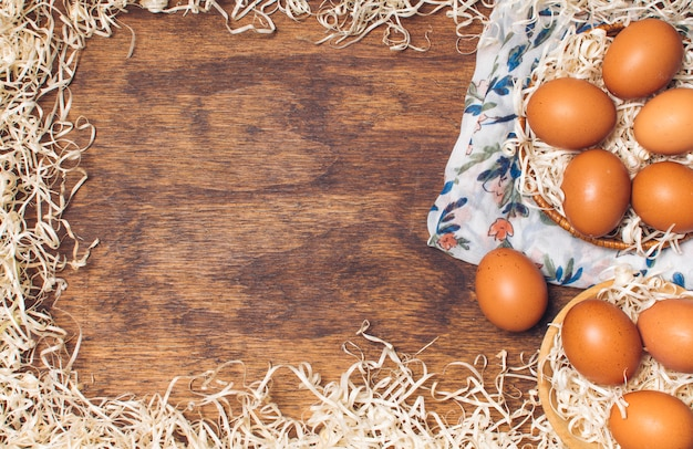 Chicken eggs in bowls on flowered material between tinsel on board Free Photo
