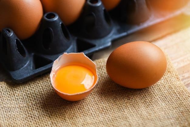 Куриные яйца из фермерских продуктов, натуральные в коробке, концепция здорового питания / свежий разбитый яичный желток Premium Фотографии