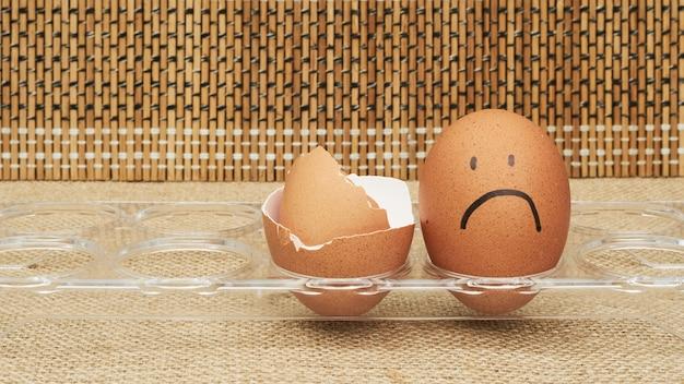 卵ホルダーに鶏の卵。半分の卵、卵黄、殻。卵に描かれた感情と表情。 Premium写真
