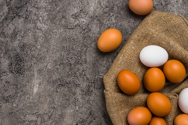 Chicken eggs scattered on brown canvas Free Photo