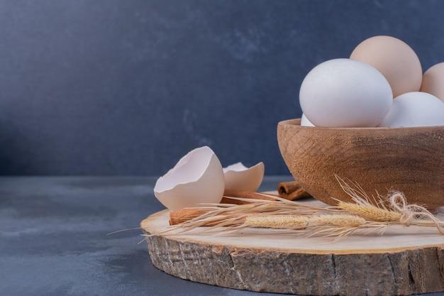 木製の大皿に卵殻と鶏卵 無料写真