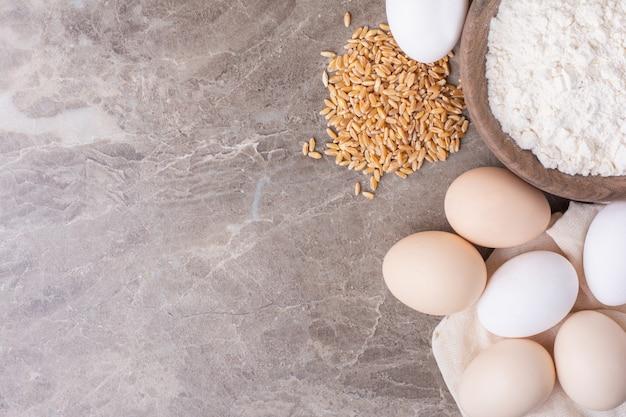 밀 곡물과 밀가루 한 컵과 닭고기 달걀 무료 사진