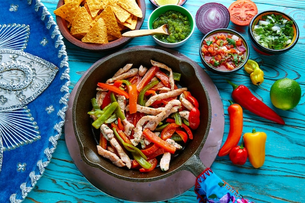 Chicken fajitas in a pan chili and sides mexican Premium Photo