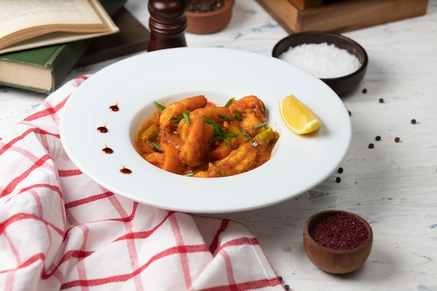 Chicken feet stew in tomato sauce in white bowl with vegetables and lemon. Free Photo