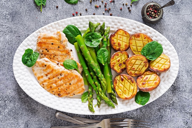 Chicken fillet cooked on a grill with a garnish of asparagus and baked potatoes. Premium Photo