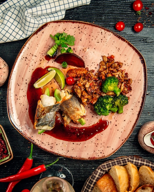 Chicken fillet rolls with nuts and green herbs and sauce inside red plate. Free Photo