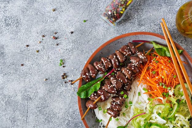 Chicken hearts in spicy sauce, noodles and vegetable salad. healthy food. top view Premium Photo