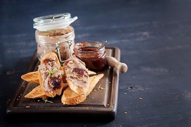 Chicken homemade liver pate in glass jar with toasts and lingonberry jam with chili. Free Photo