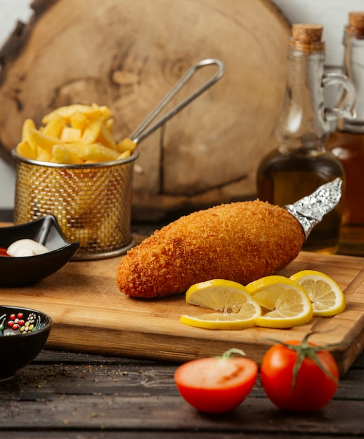 Chicken kiev served with fries, lemon, mayonnaise and ketchup Free Photo