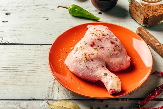 さまざまなスパイスと木製の表面上のオレンジ色のプレート上の鶏の脚の四分の一 Premium写真
