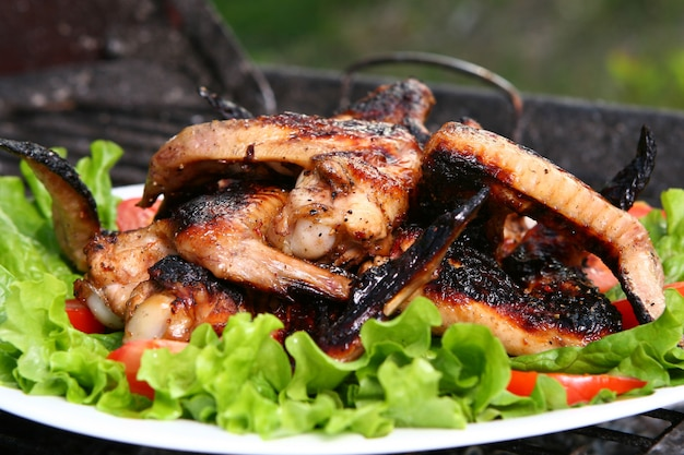 Chicken legs on the grill with vegetables Free Photo