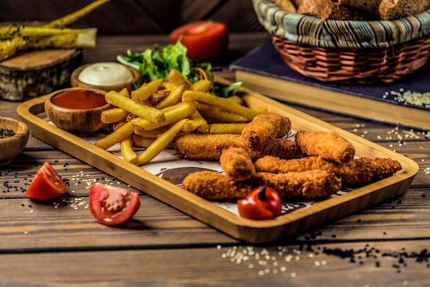 Chicken legs with crispy potato fries. Free Photo