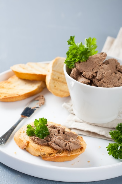 Chicken liver pate on bread and in bawl Premium Photo