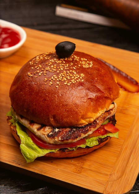 Chicken meat burger with tomato slices and lettuce served with , ketchup and mayonnaise on wooden board Free Photo