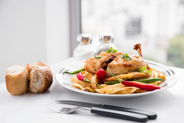 Chicken meat garnished by vegetables beside bread Free Photo