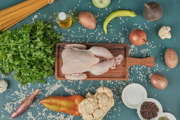 파스타와 야채 주위 나무 보드에 닭고기. 무료 사진
