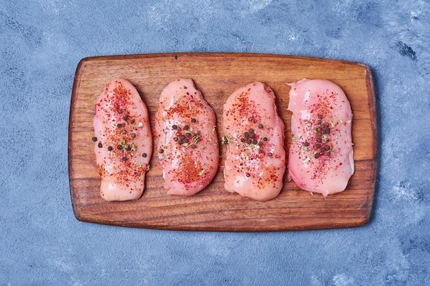 Куриное мясо со специями на деревянной доске на синем Бесплатные Фотографии