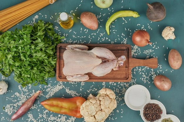 Chicken meat on a wooden board with pasta and vegetables around. Free Photo