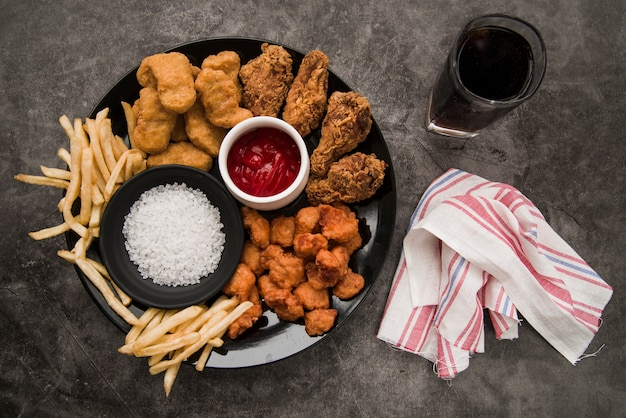 Chicken nuggets; fried chicken drumstick; crispy chicken popcorn; french fries with softdrink and napkin on concrete background Free Photo