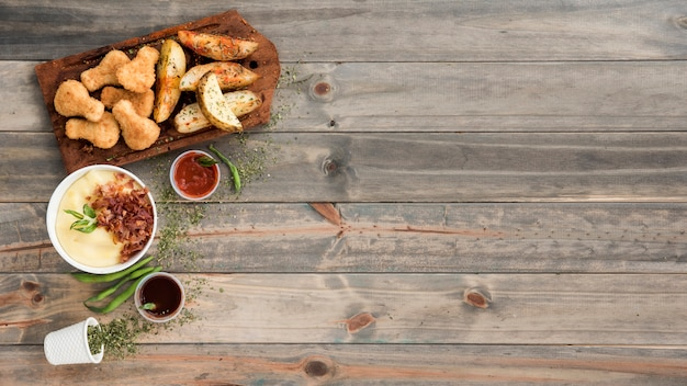 Chicken nuggets and potato wedges on wooden board Free Photo