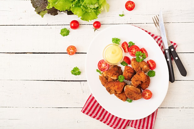 Chicken nuggets and sauce in plate on a white wooden table Premium Photo