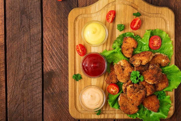 Chicken nuggets and sauce on a wooden table Premium Photo