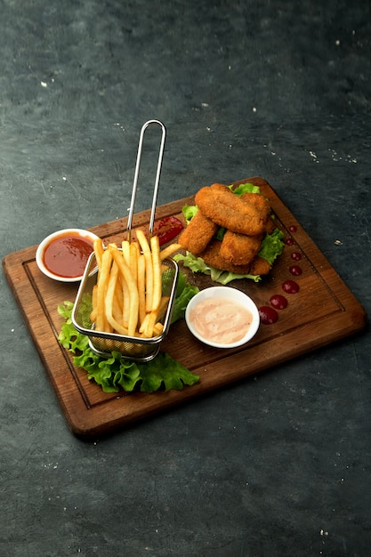 Chicken nuggets with fries and sauces Free Photo