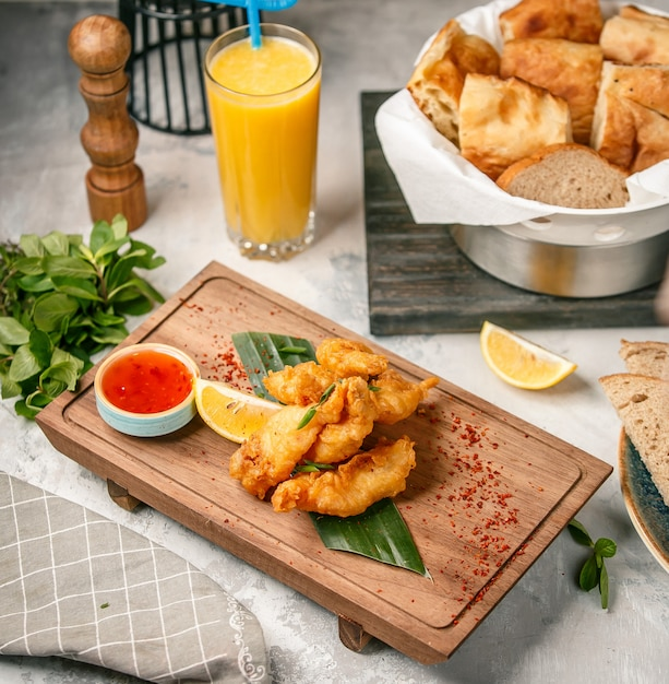 Chicken nuggets with sauce on wooden board Free Photo