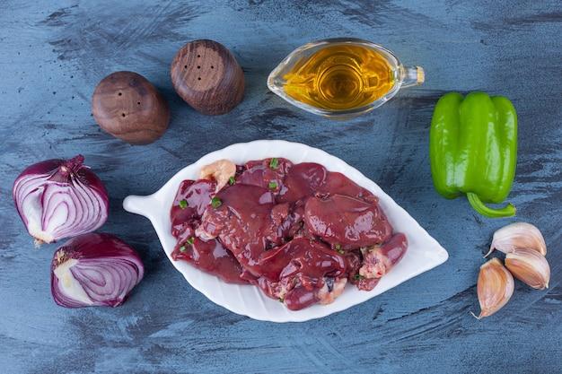 플래터에 닭고기 내장, 기름 그릇, 소금 양파, 마늘, 후추 파란색 표면에 무료 사진